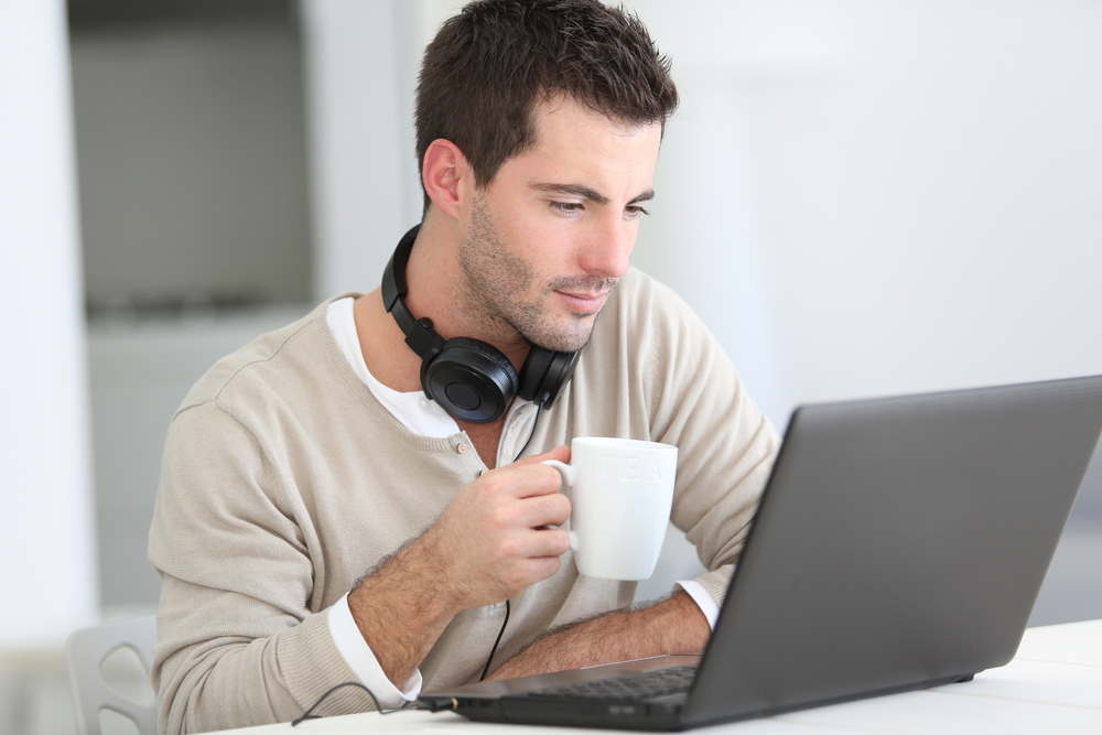 Man in front of laptop computer with headset