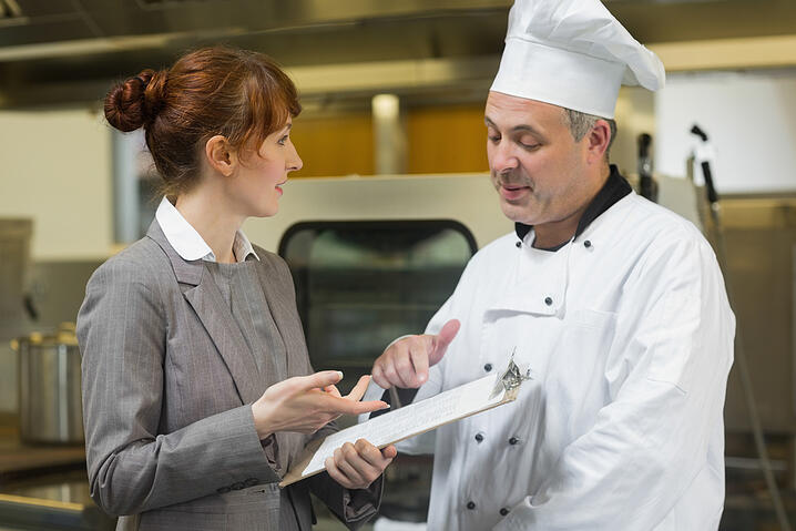 Young female inspector talking to the head cook standing in a professional kitchen